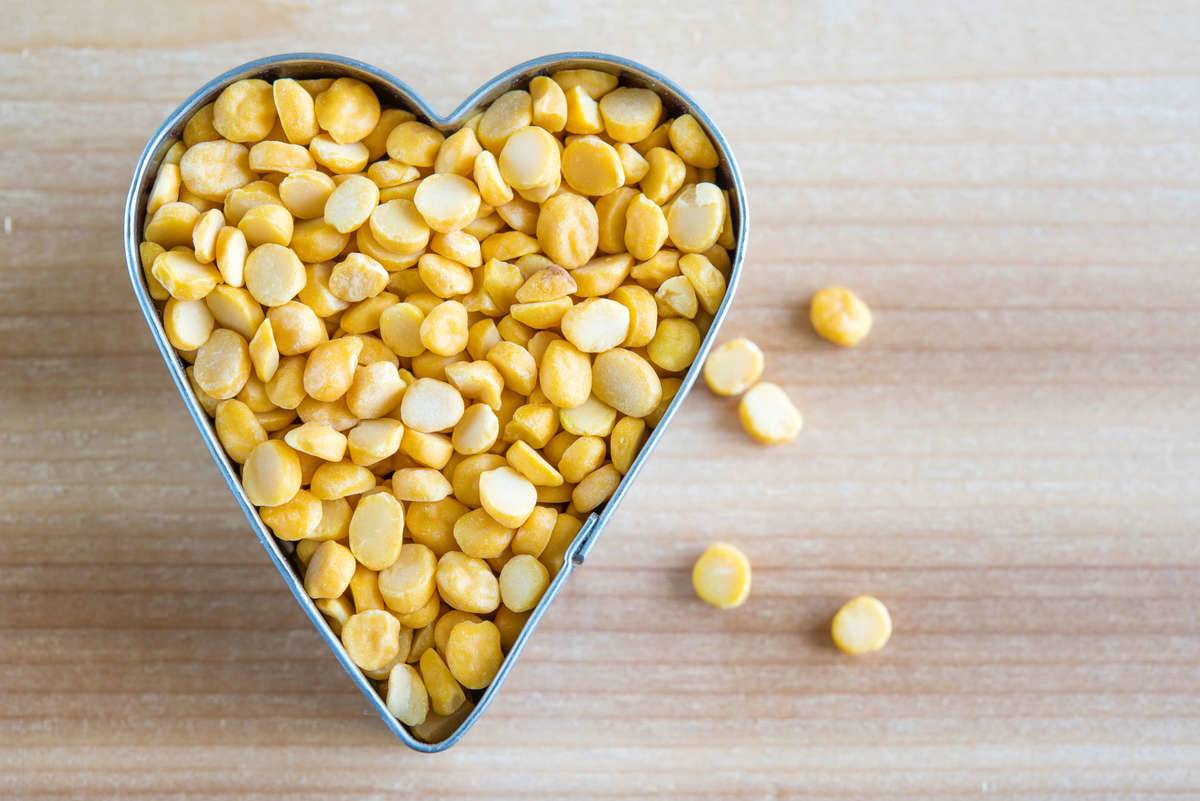 Yellow lentils are contained inside of a heart-shaped cookie cutter.
