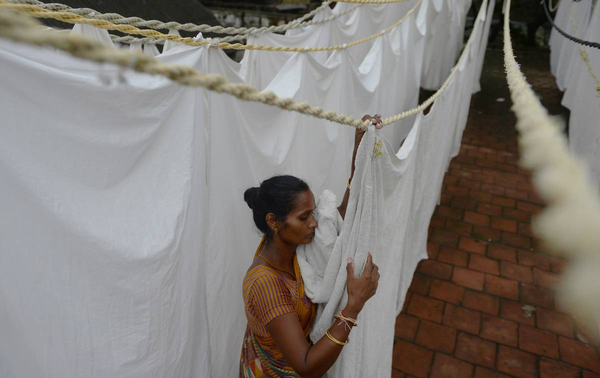 A woman hangs bed sheets to dry in India.