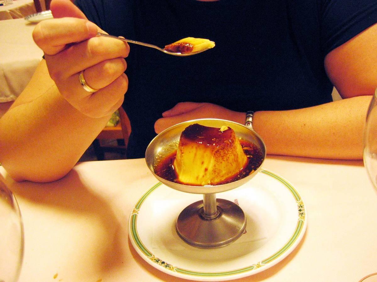 A woman eats custard at a restaurant.