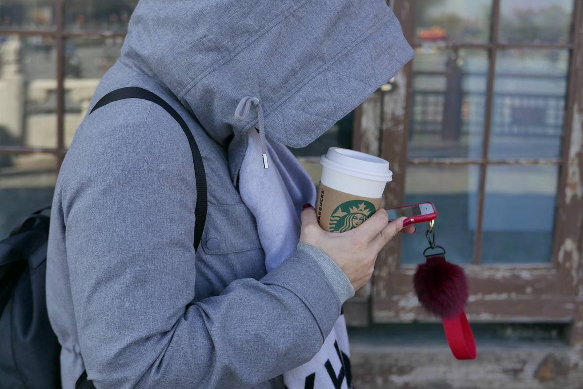 A girl with her hood up walks down the street with a Starbucks cup.