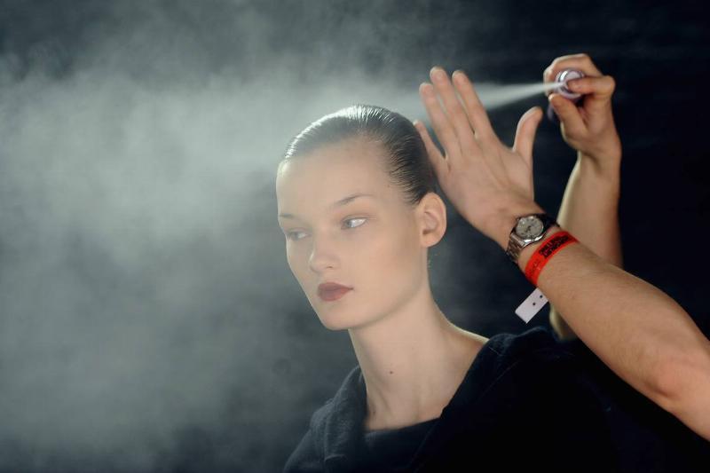 A person sprays hair spray on a model.