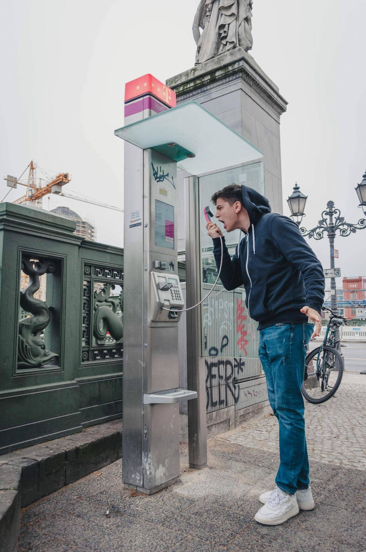A man angrily shouts at a pay phone.