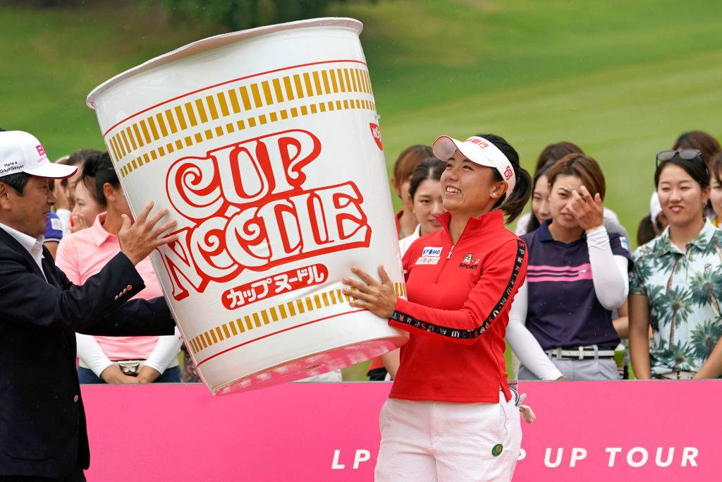 a golfer holding a giant Cup Noodle