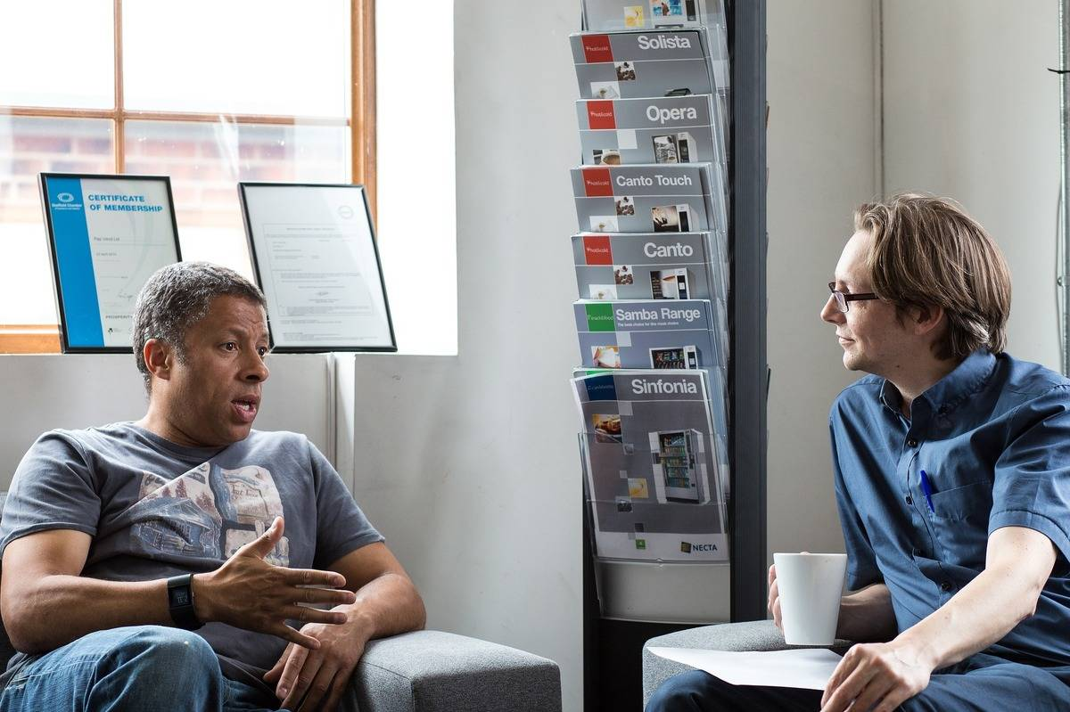 Two men chat in an office.