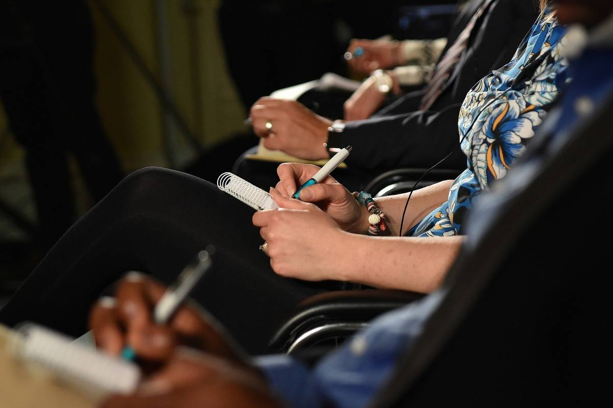 Women take notes during a meeting.
