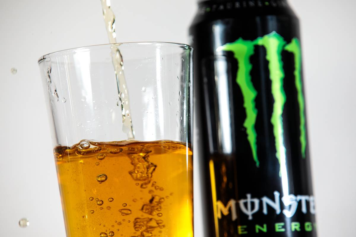 Monster energy drink gets poured into a glass.