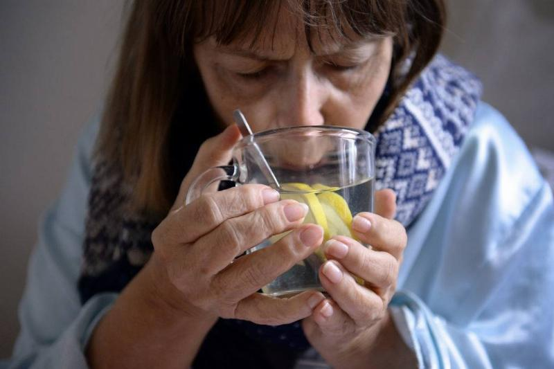 A woman drinks lemon water.