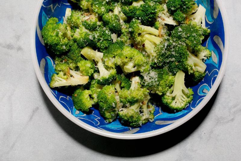 Seasoned broccoli is seen on a blue plate.