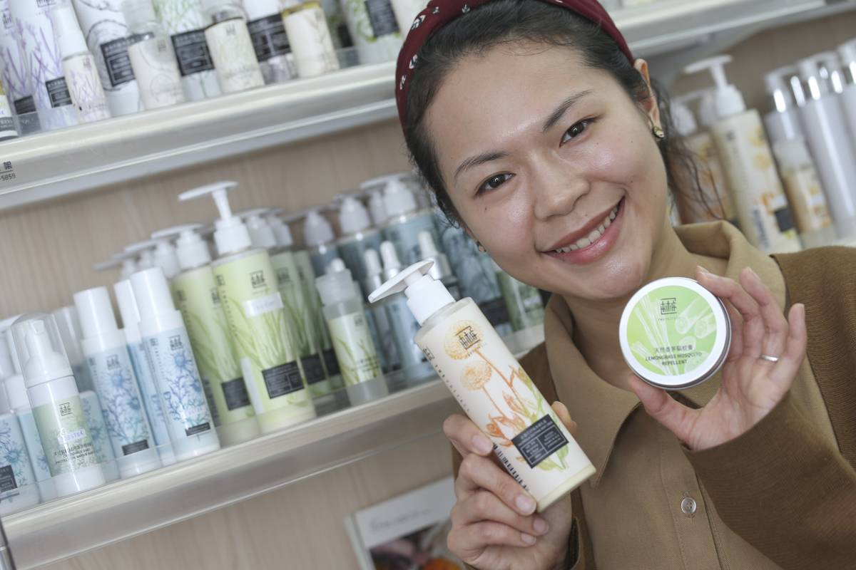 A woman holds up skincare products made with calendula.