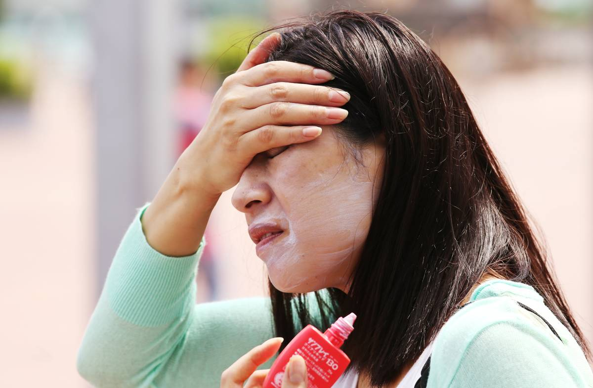 A woman rubs sunscreen on her face.