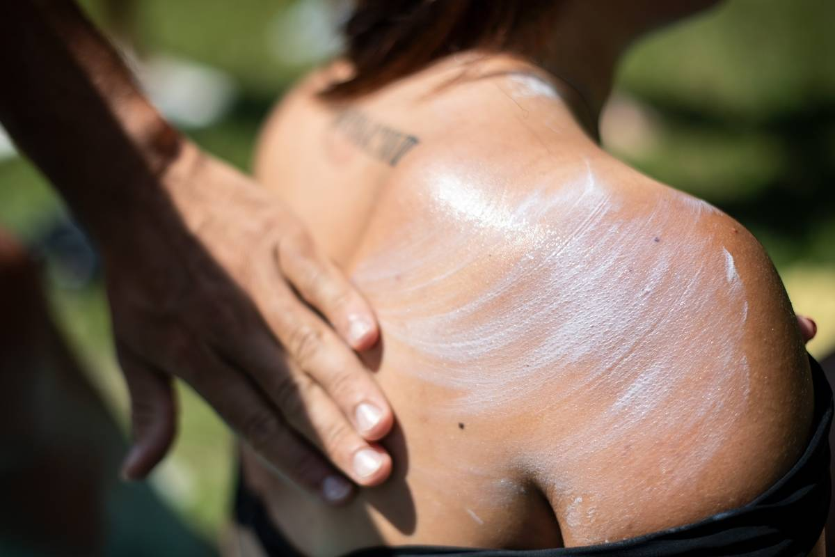 A person rubs sunscreen on a woman's back.