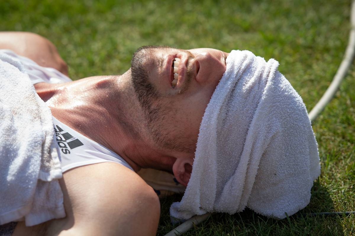 A man lies down with a damp towel over his eyes and head.