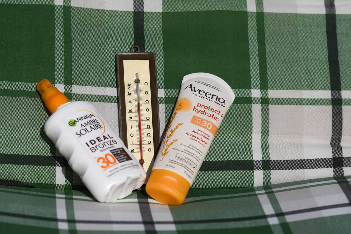 Sunscreen bottles and a thermometer close to 40 ° C sit on a chair.