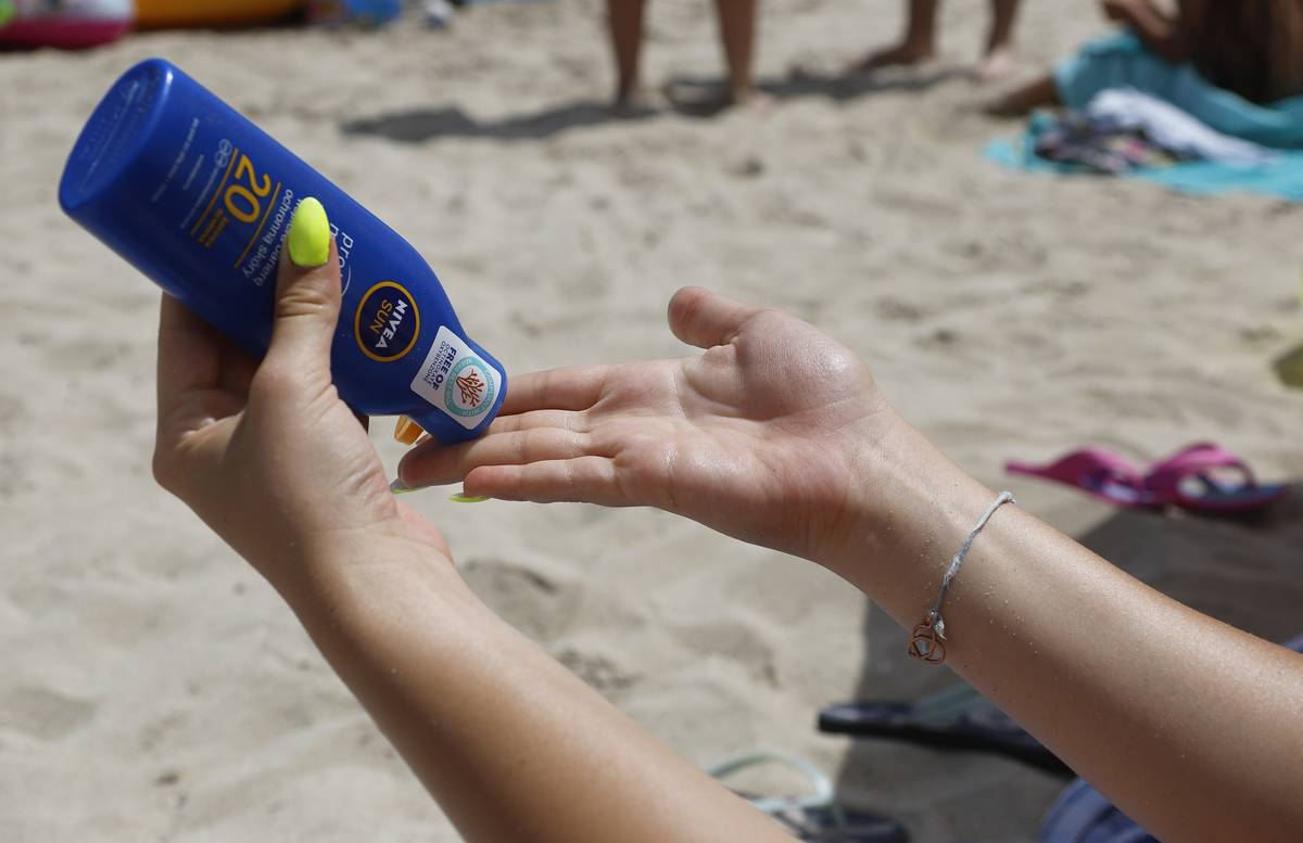 A woman pours sunscreen on her hand at the beach.