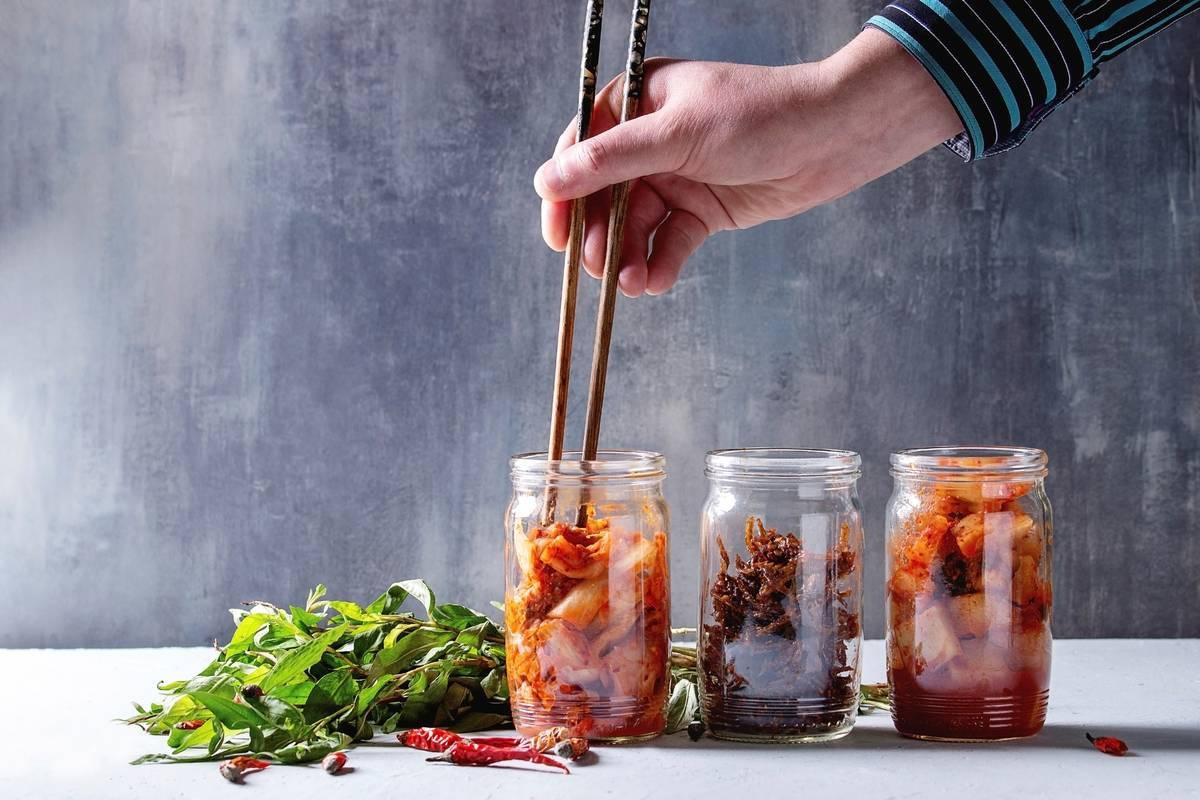 A person removes kimchi from a mason jar using chopsticks.
