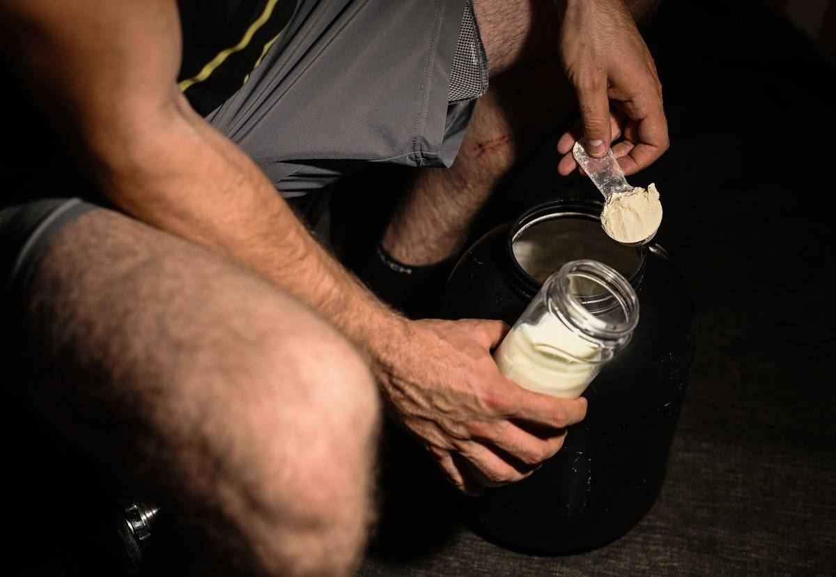 A man scoops protein powder into a cup.