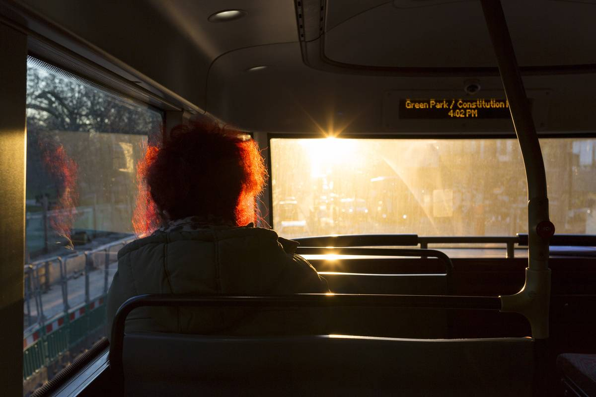 The sun shines through the window of a bus.