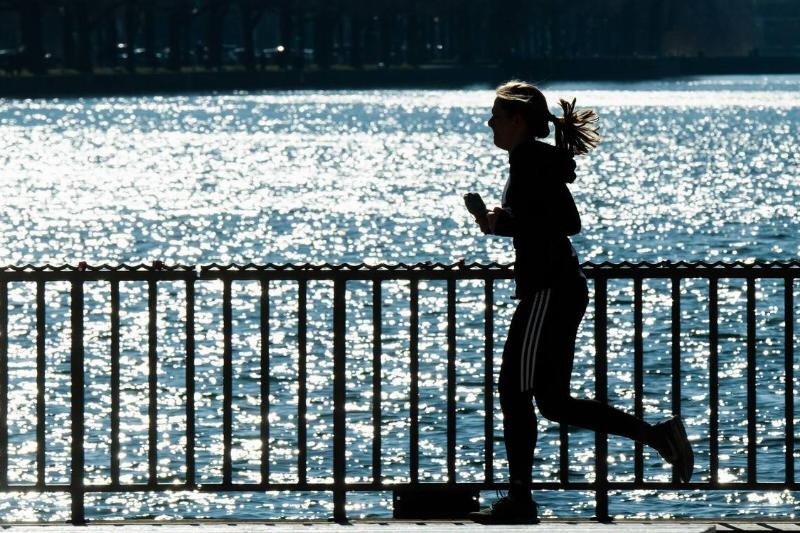 The silhouette of a woman jogs next to the water on a sunny day.