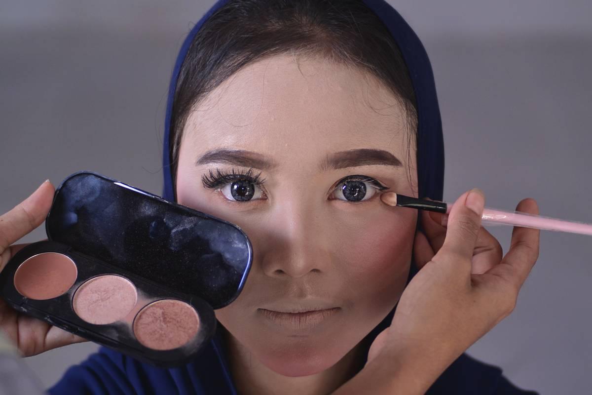 A woman applies face makeup.