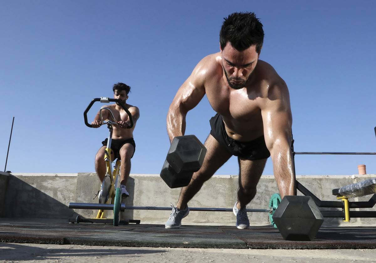 Two bodybuilders work out outside.