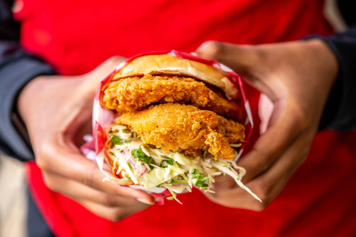A person holds a fried chicken sandwich with slaw.