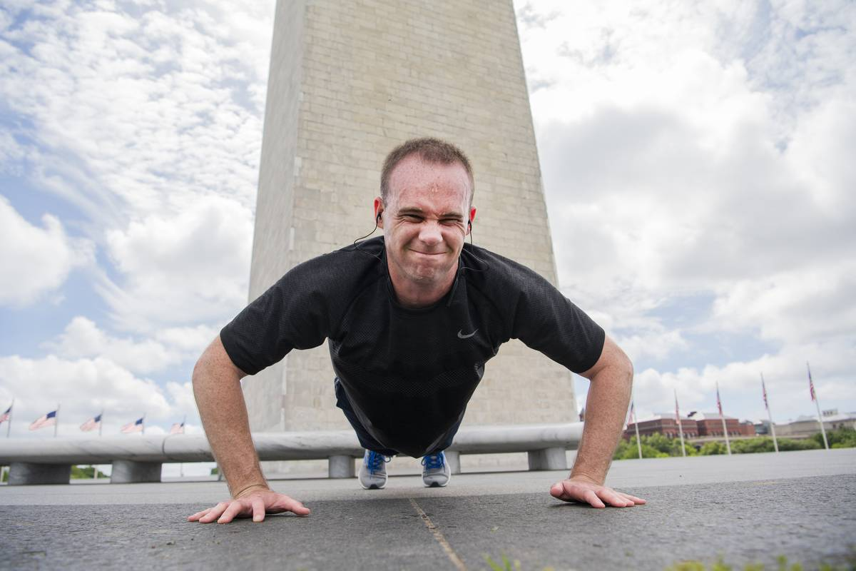A man does push-ups in front of the Washington Monument.