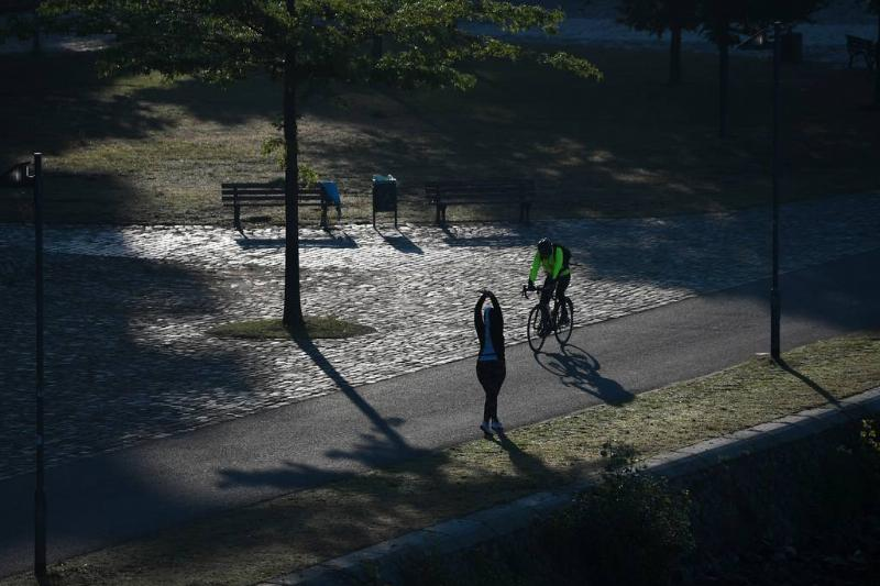 A bicyclist and a jogger meet during a morning workout.