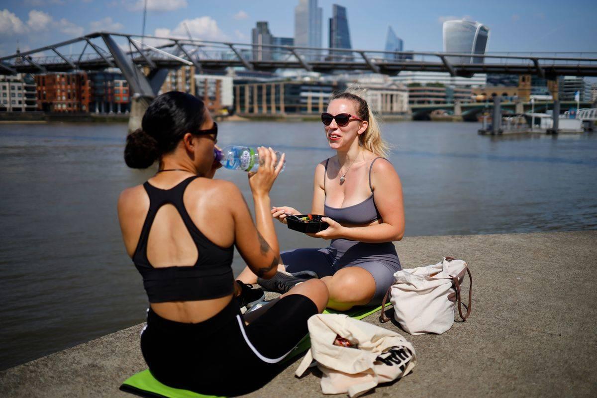 To women eat lunch beside a river outside.