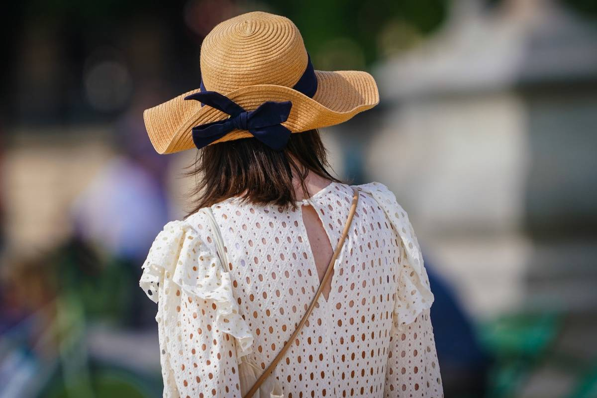 A woman wears a blouse and summer hat in Paris.
