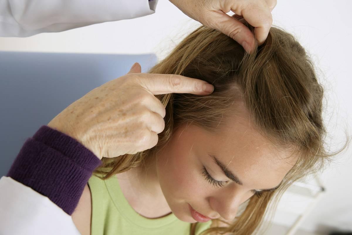 A doctor checks a woman's hair.