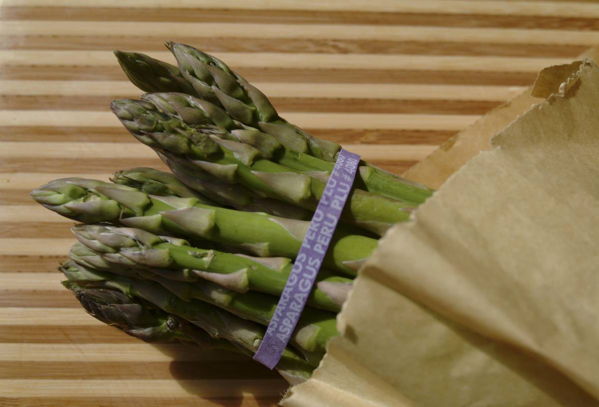A bunch of asparagus is wrapped in a paper bag.