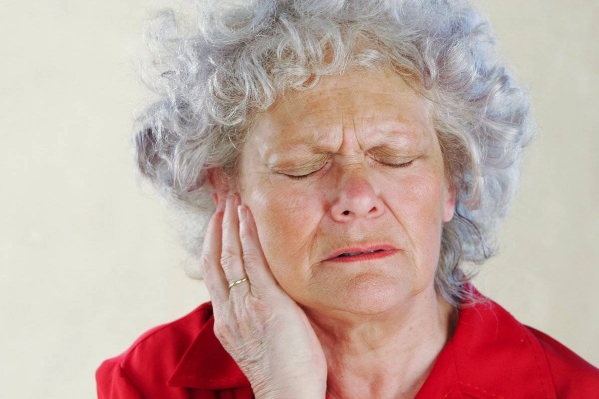 An older woman clutches her ear in pain.