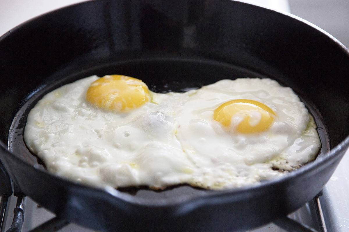 Two eggs are fried in a skillet.