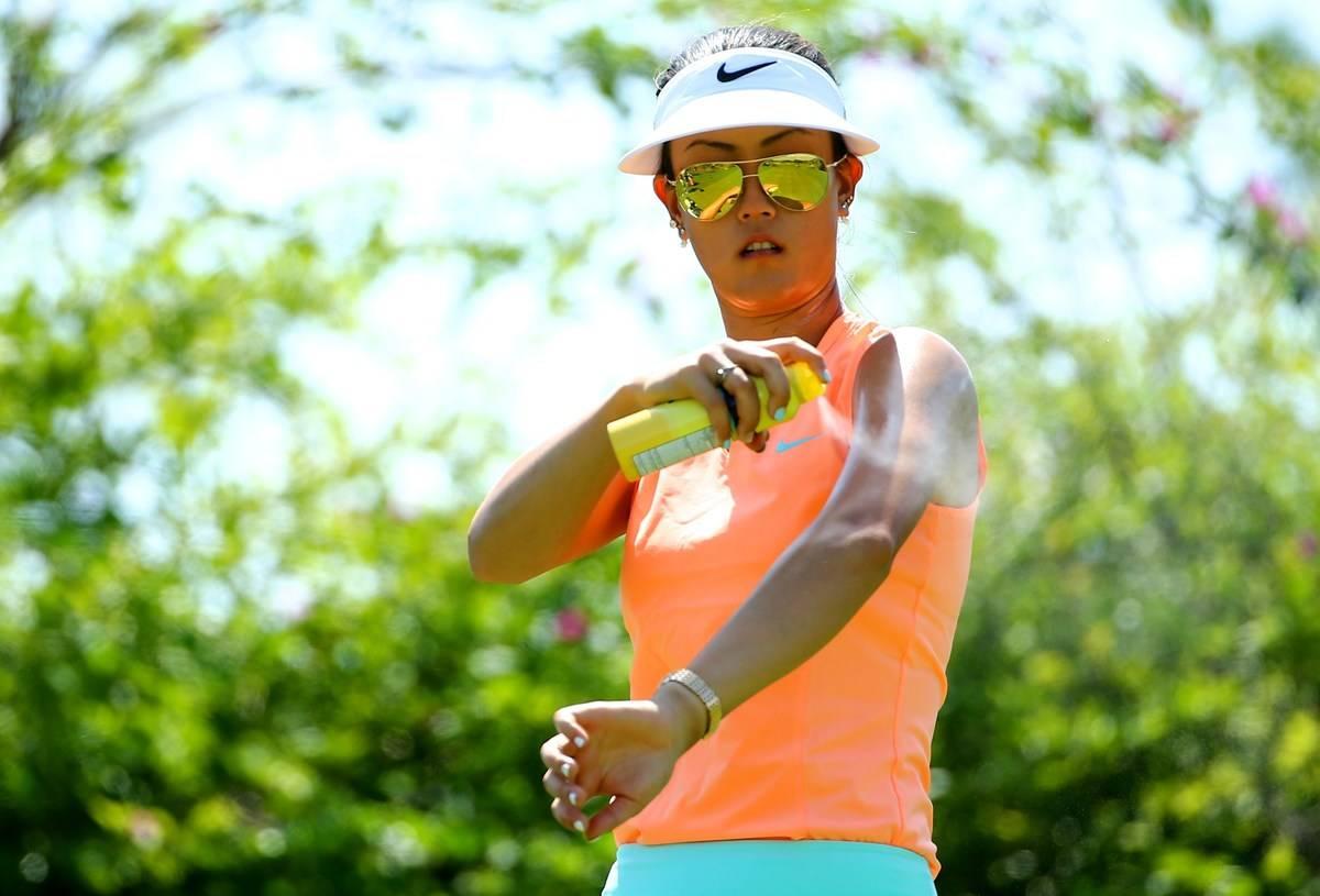 A tennis player sprays sunscreen on her arm.