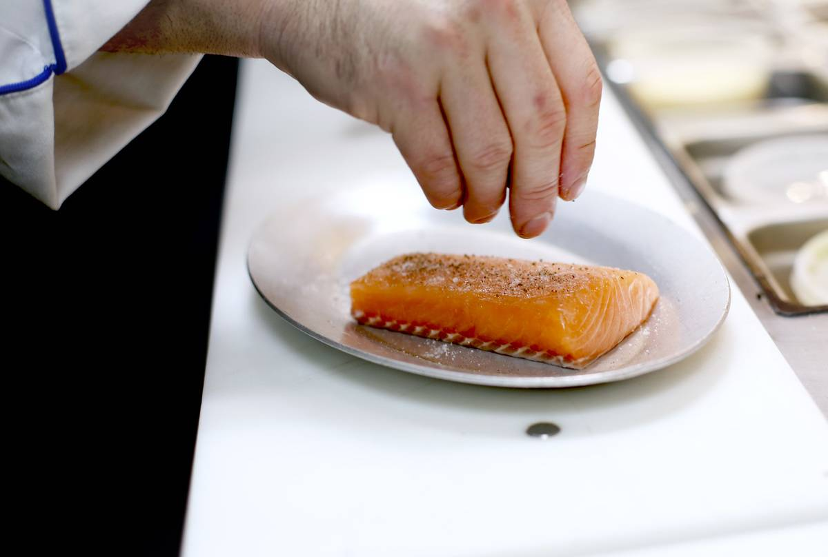 A chef sprinkles herbs on raw salmon.