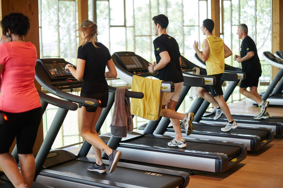 Gym members run on treadmills while looking outside.