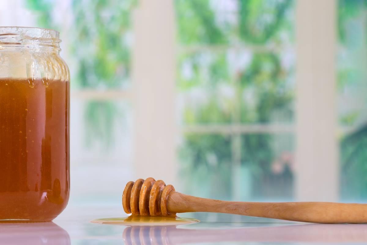 A jar of honey is seen next to a honey dipper.