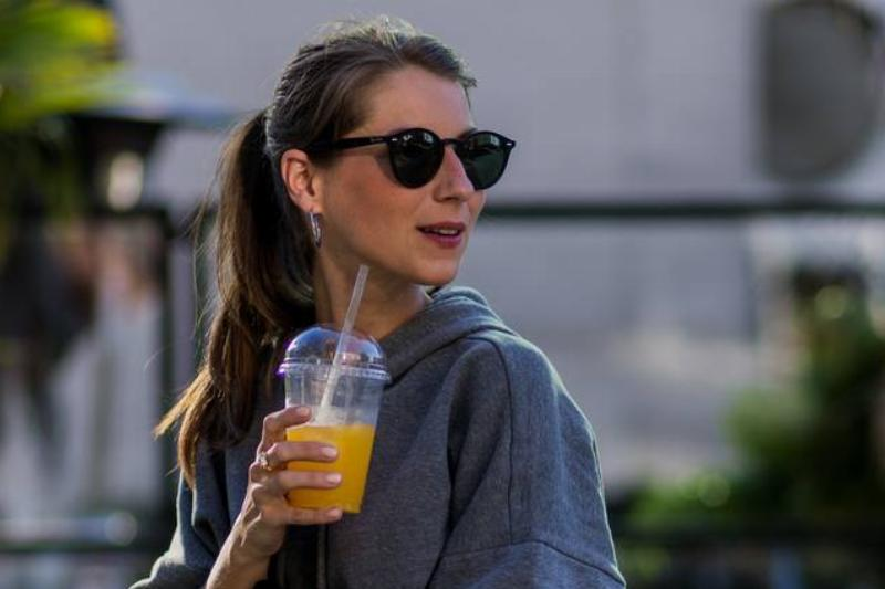 A woman drinks orange juice.
