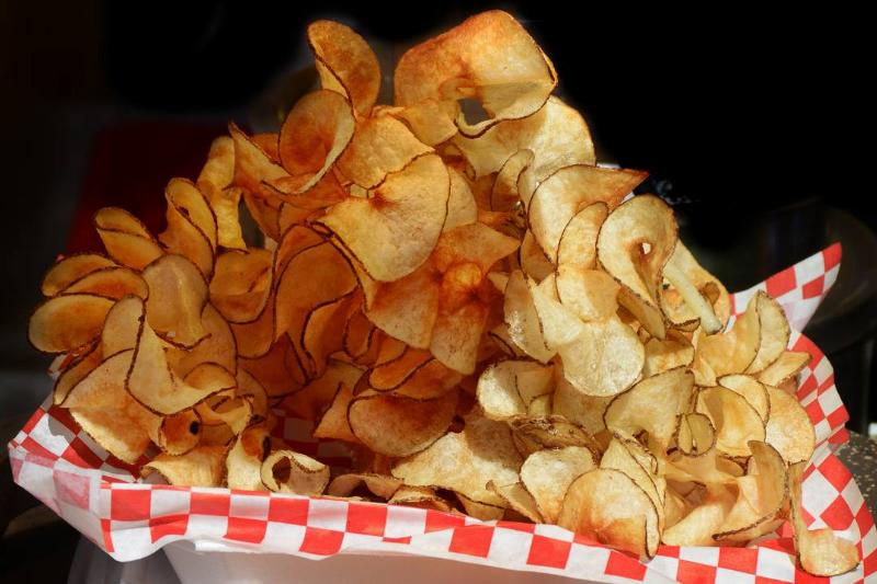 Potato chips are piled onto a plate at a Spanish Market.