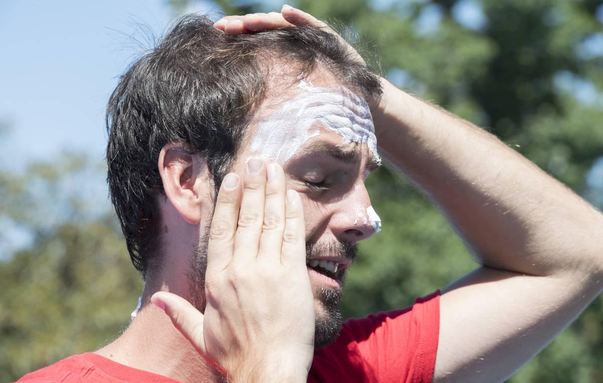 A man rubs sunscreen on his face.