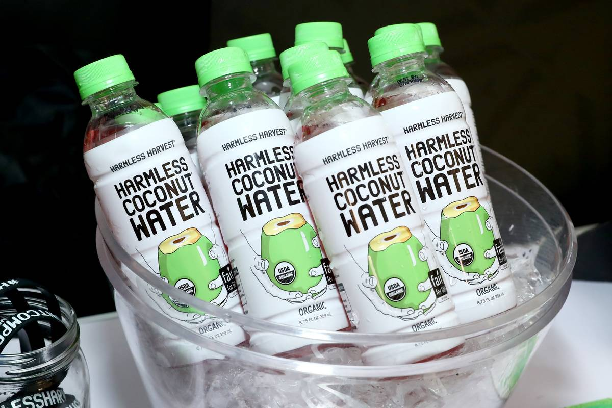 A container holds bottles of coconut water.