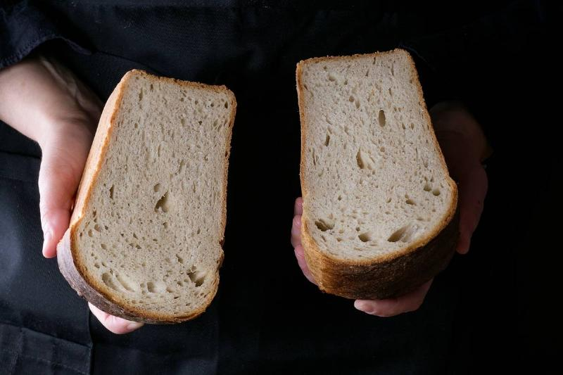 A woman holds two slices of white bread.