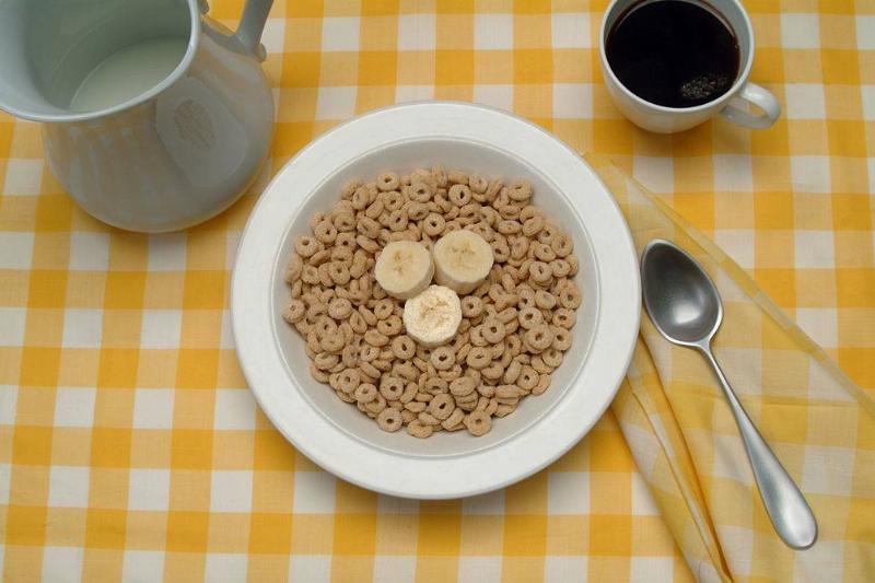 View of a table setting with a bowl of breakfast cereal (and banana slices), a cup of coffee, and a pitcher of milk