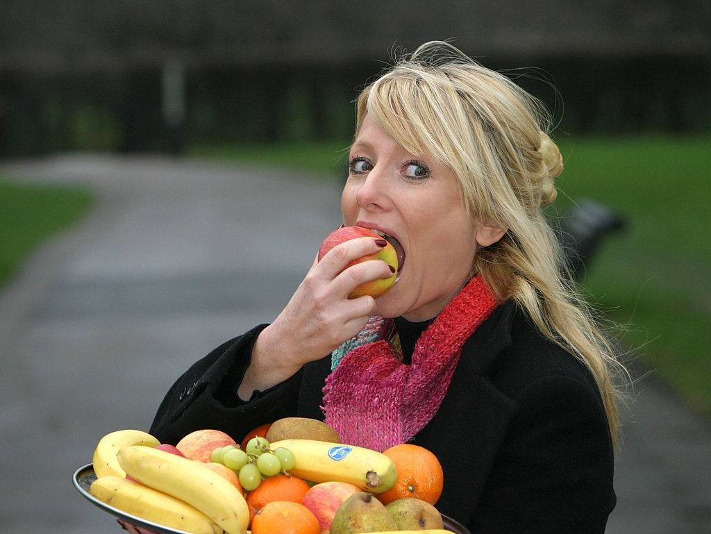a woman taking a bite out of an apple
