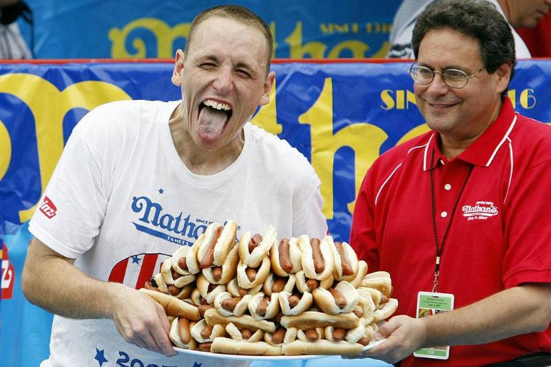 Joey Chestnut holding a plate of 66 hot dogs