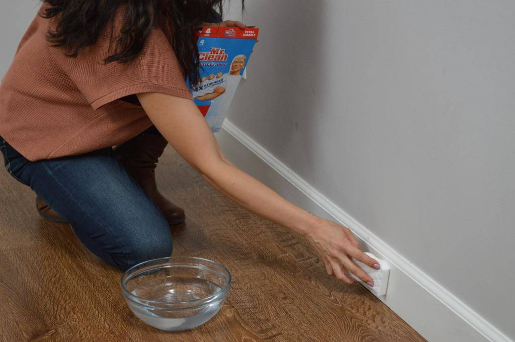 A woman rubs a wall with Mr. Clean's magic eraser.