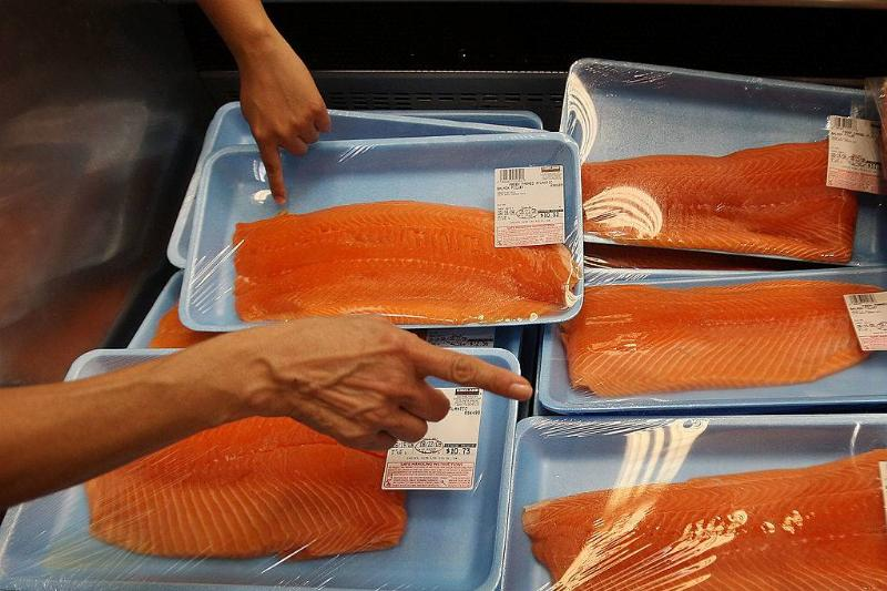 people picking out salmon at a grocery store