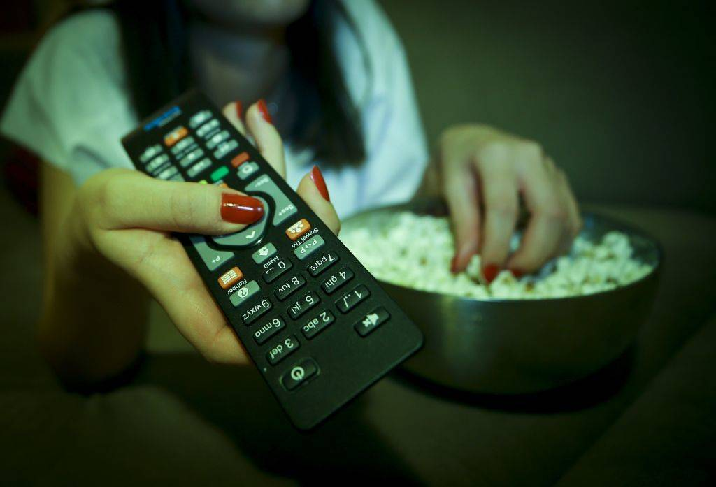 A woman holds a remote controller while eating popcorn