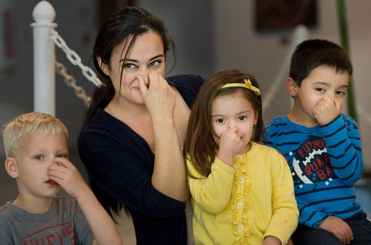 A mother and her children pinch their noses.