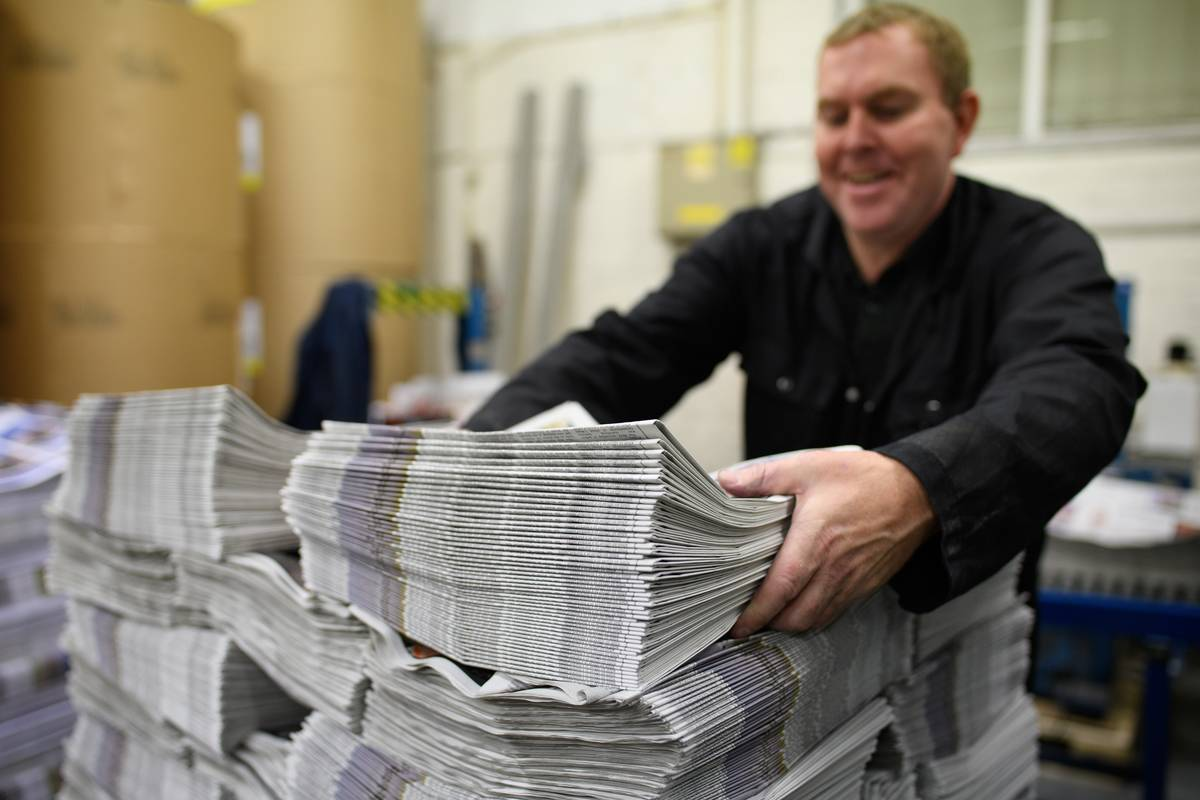 A person picks up stacks of newspapers.